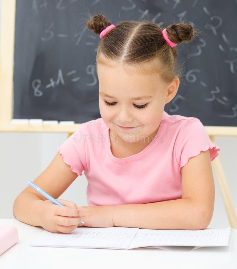 Liten flicka är writing genom att använda en penna royaltyfri foto
