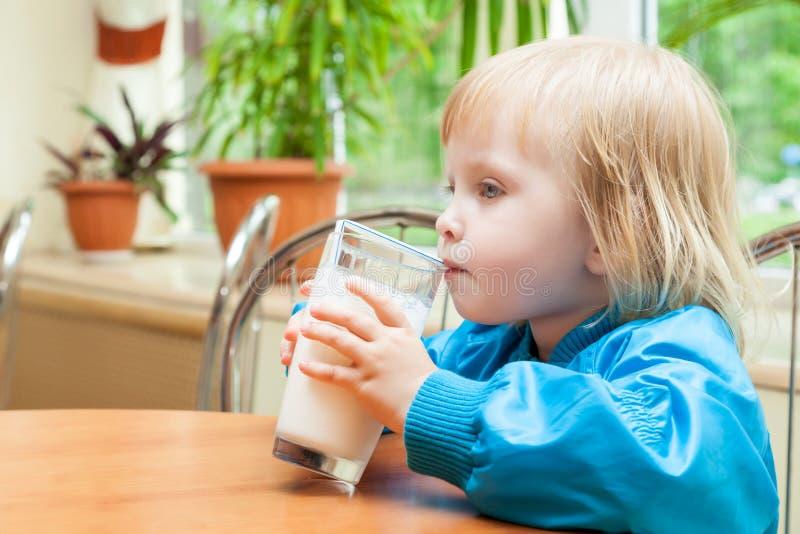 Liten flicka dricker mjölkar arkivbild