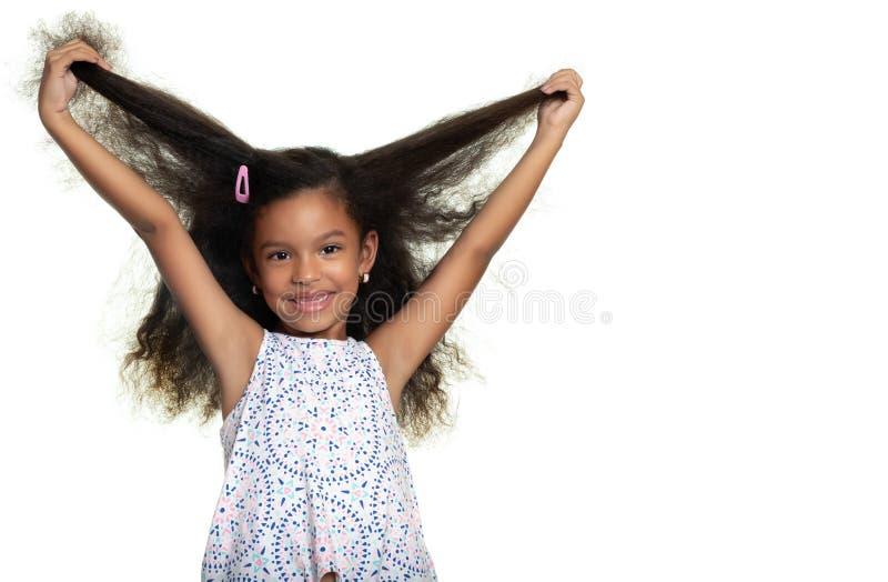 Liten flicka för gullig afrikansk amerikan som spelar med hennes långa lockiga hår royaltyfria foton