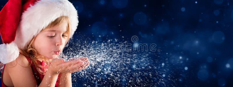 Liten flicka för julönskabegrepp som blåser snö - julönskabegrepp fotografering för bildbyråer