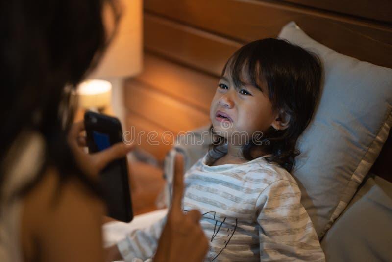 Liten flicka för ståendemodervarning inte till mer leklek royaltyfri foto