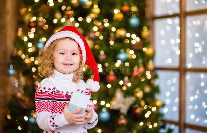 Liten flicka i ask för gåva för röd santa hatt hållande royaltyfri fotografi