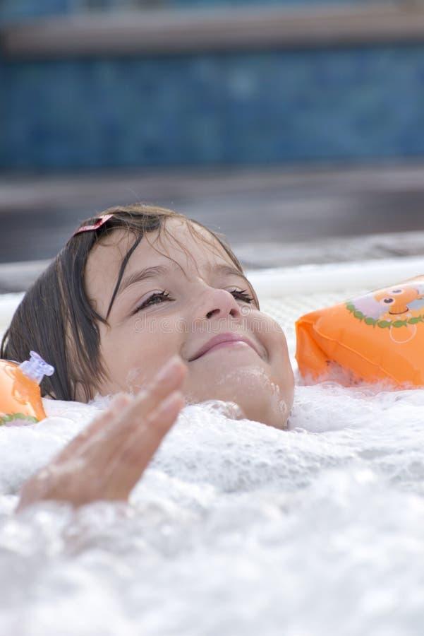 Liten flicka i bubbelpool royaltyfri foto