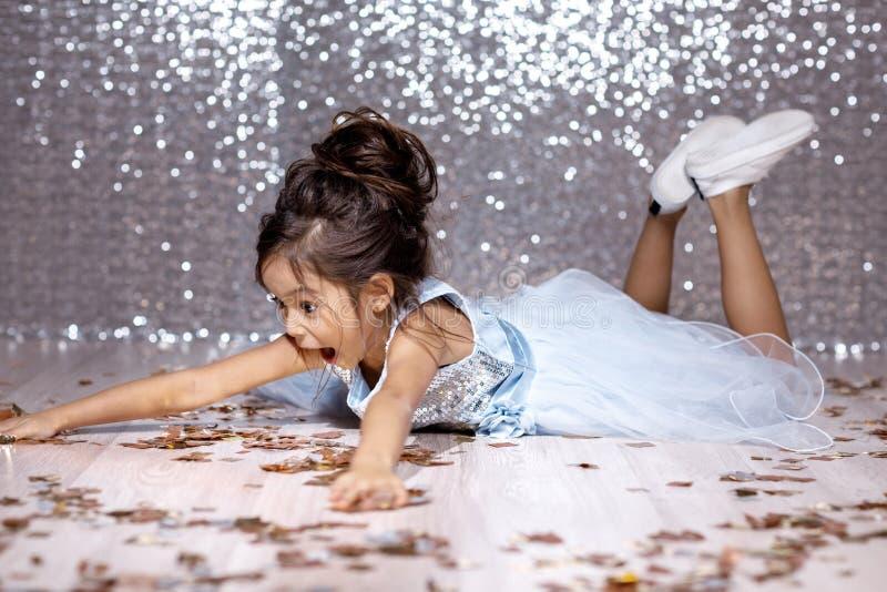 Liten flicka i den blåa klänningen som sitter på golvet med konfettier arkivfoton