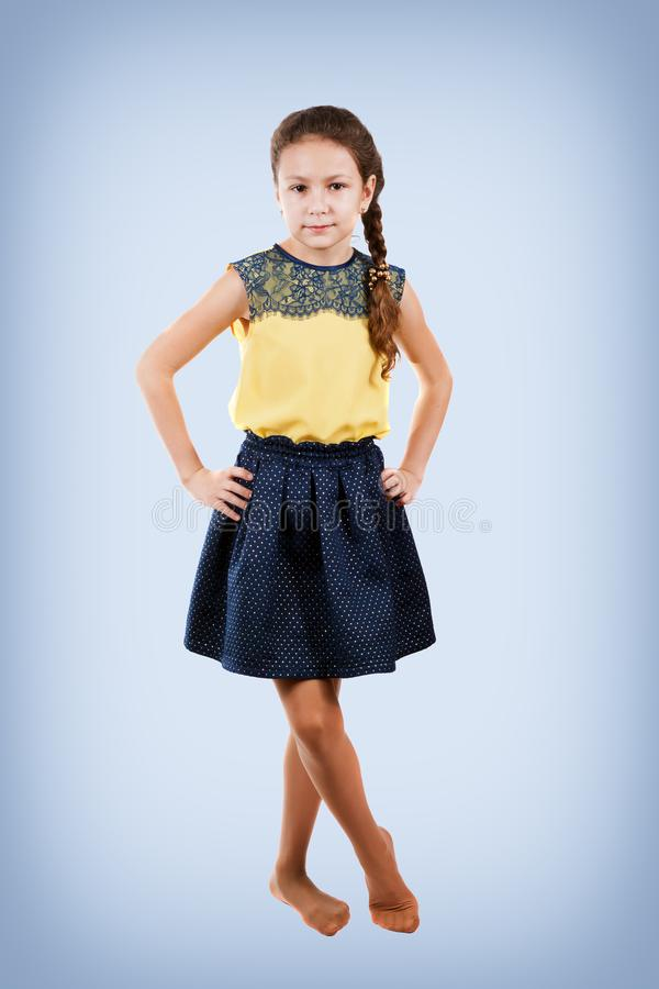 Liten flicka i den gula blusen som in camera poserar arkivfoto
