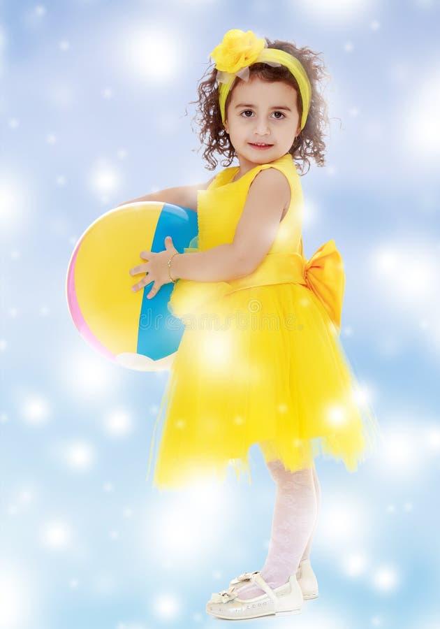 Liten flicka i den gula klänningen som rymmer en boll arkivbild