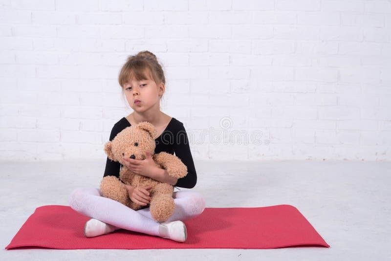 Liten flicka i den gymnastiska baddräkten och med en nallebjörn, fritt utrymme royaltyfri foto