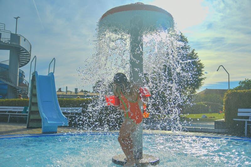Liten flicka i den lilla simbassängen Den gulliga flickatagandeduschen i vatten parkerar Sommar och lyckligt chilhoodbegrepp arkivbilder