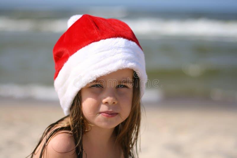 Liten flicka i den röda hatten Santa Claus på stranden arkivbild