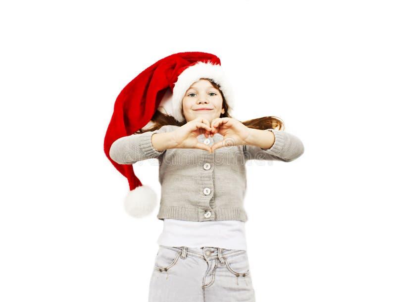 Liten flicka i den röda jultomtenhatten som gör hjärtan med henne händer arkivfoton