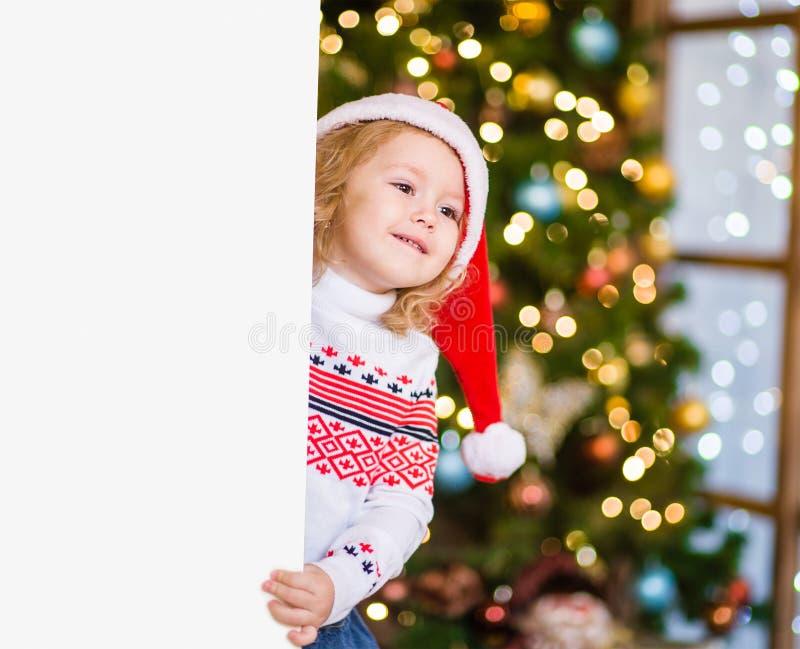 Liten flicka i den röda santa hatten bak det vita brädet Utrymme för text royaltyfri fotografi