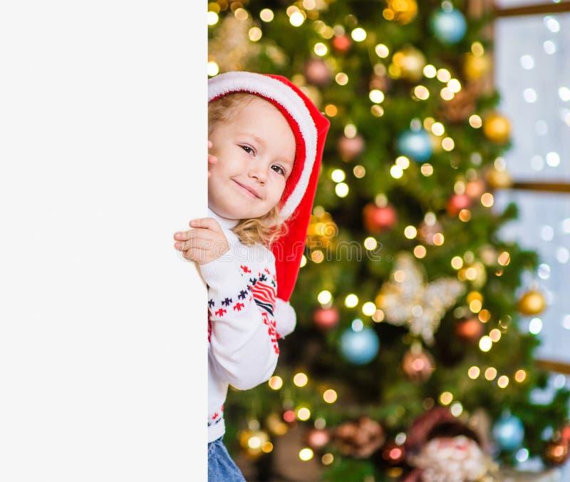Liten flicka i den röda santa hatten bak det vita brädet Utrymme för text fotografering för bildbyråer