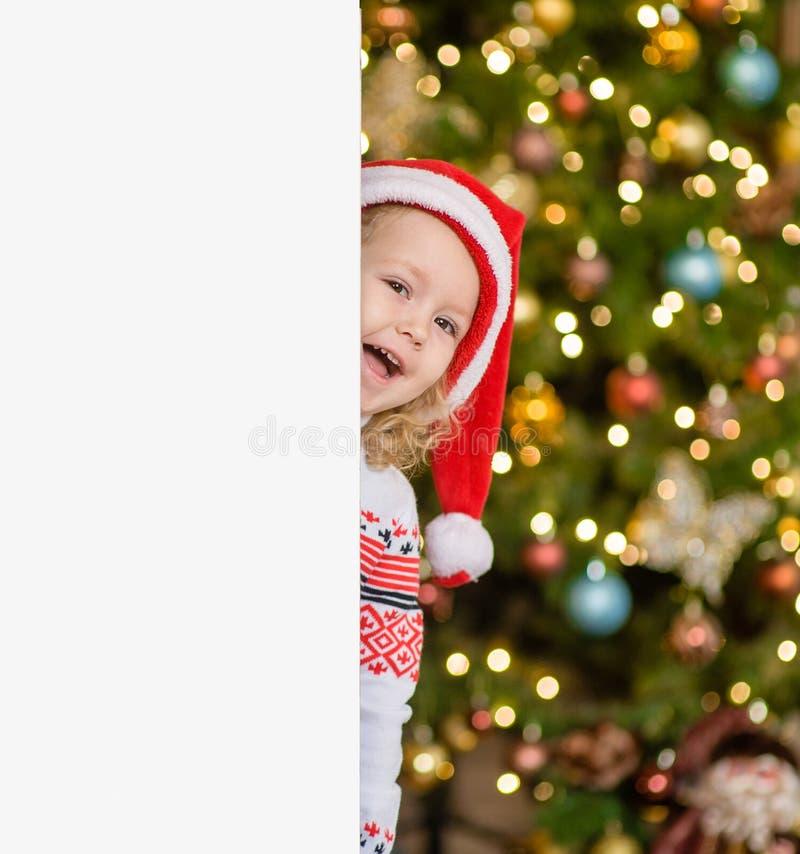 Liten flicka i den röda santa hatten bak det vita brädet Utrymme för text royaltyfri bild