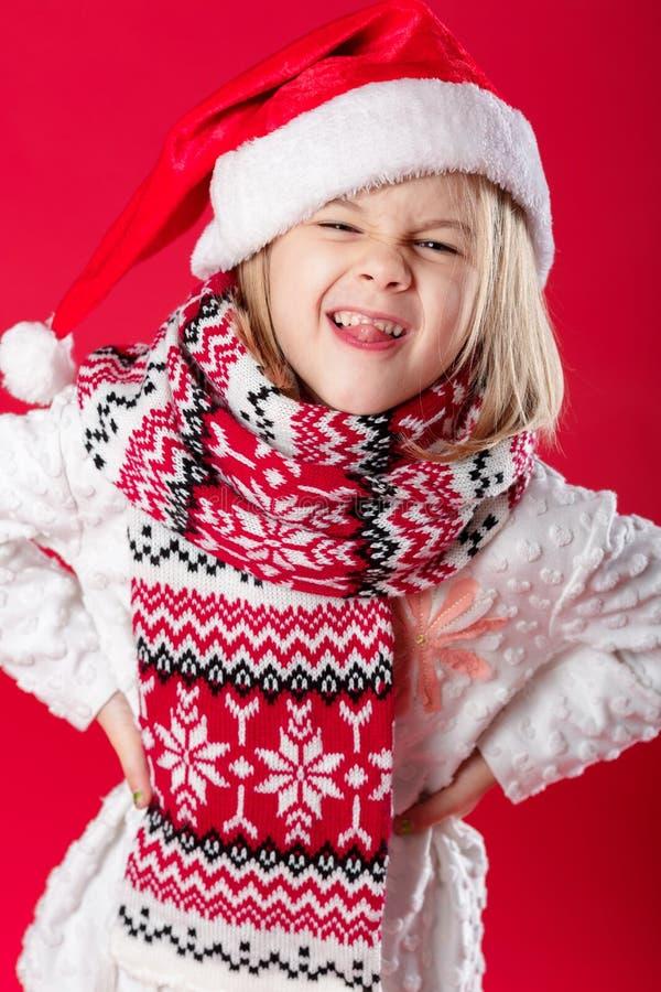 Liten flicka i den santa hatten och halsduken på röd bakgrund royaltyfri fotografi