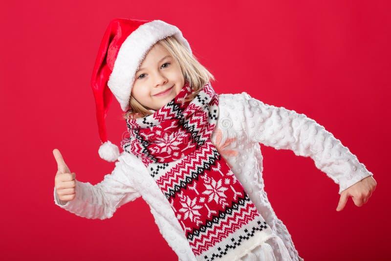 Liten flicka i den santa hatten och halsduken på röd bakgrund fotografering för bildbyråer