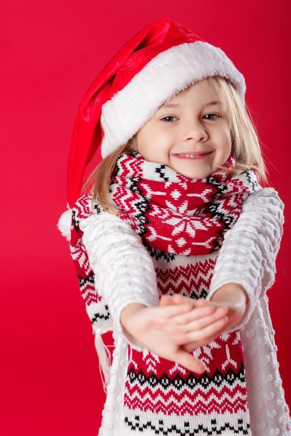 Liten flicka i den santa hatten och halsduken på röd bakgrund arkivbilder