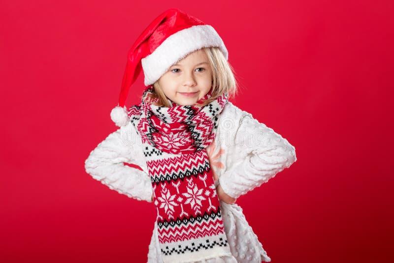 Liten flicka i den santa hatten och halsduken på röd bakgrund royaltyfria bilder