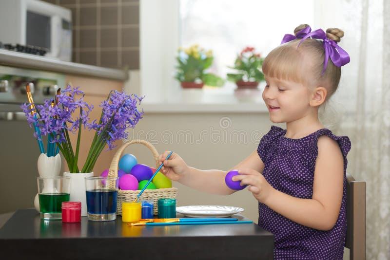 Liten flicka i den violetta klänningen som dekorerar easter ägg
