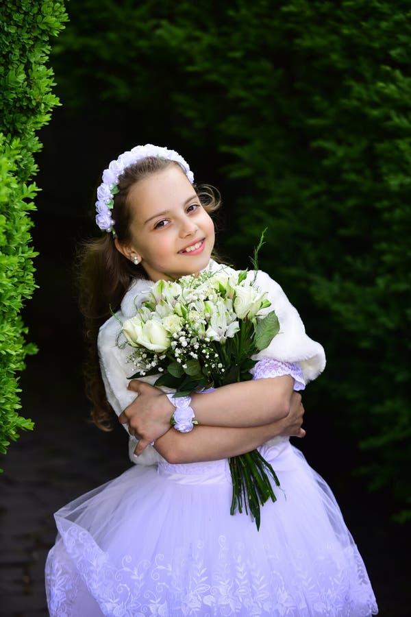 Liten flicka i den vita klänningen med rosblommabuketten royaltyfri foto
