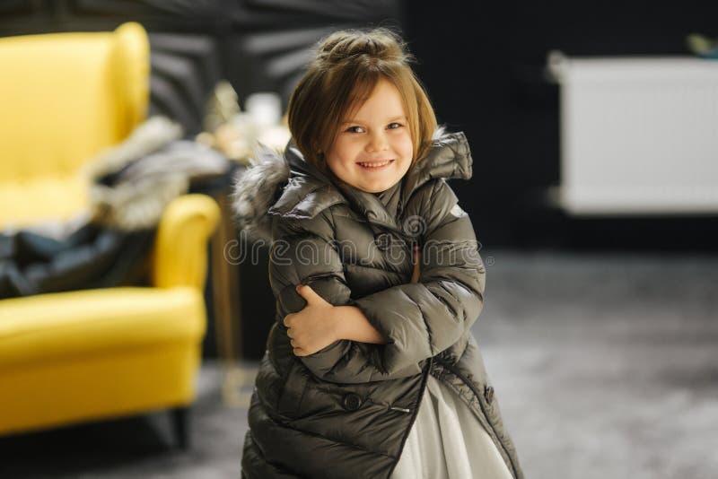 Liten flicka i den vita klänningen och jaket på studion Lyckligt flickaleende royaltyfri fotografi