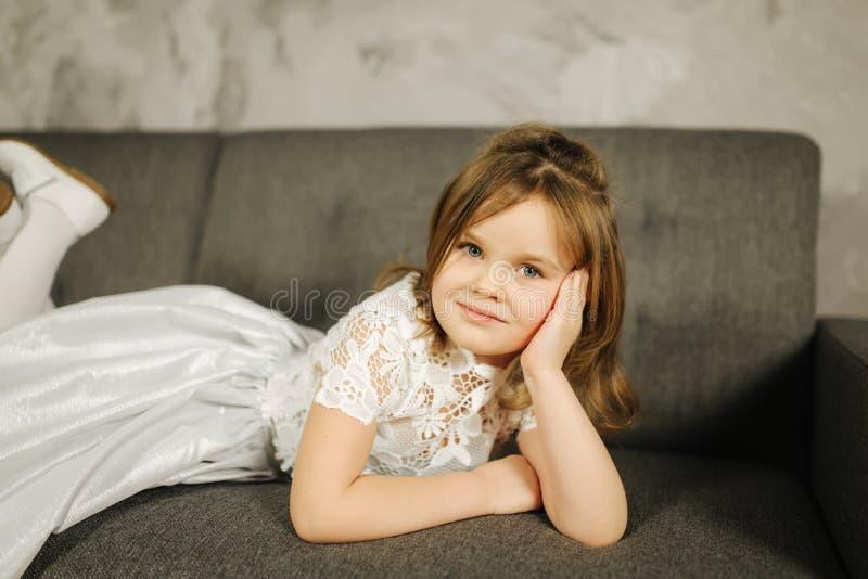 Liten flicka i den vita klänningen på soffan Fem - årsflicka hemma fotografering för bildbyråer