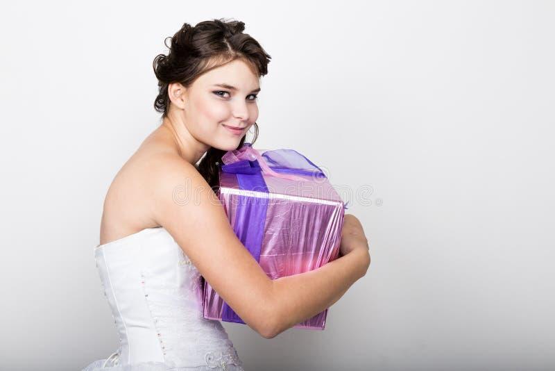 Liten flicka i den vita klänningen som rymmer en ask med gåvan arkivbild