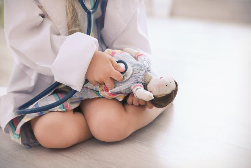 Liten flicka i det medicinska laget som spelar med dockan royaltyfri fotografi