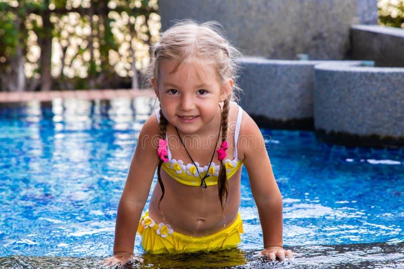 Liten flicka i en gul baddräkt i en blå pöl som en sjöjungfru ungar begrepp, ungemode royaltyfri bild