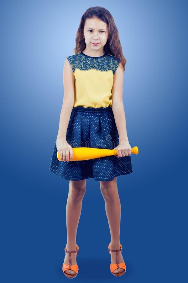 Liten flicka i en gul blus med ett gult leksakbaseballslagträ arkivfoto