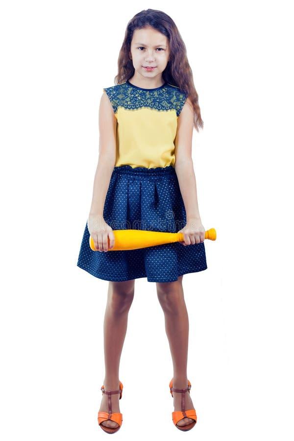 Liten flicka i en gul blus med ett gult leksakbaseballslagträ arkivbild