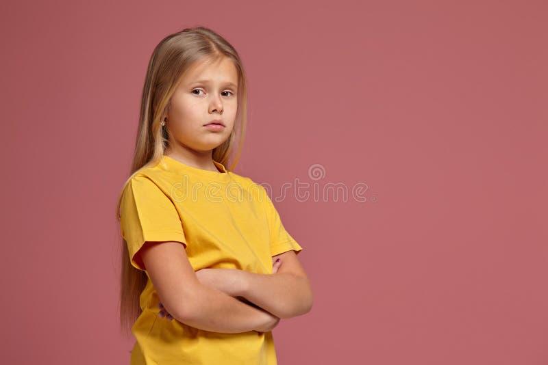 Liten flicka i en gul T-tröja kränkta blickar royaltyfri bild