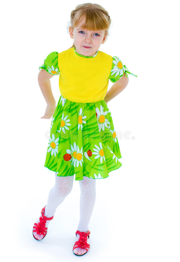 Liten flicka i en härlig grön klänning som poserar med tusenskönor royaltyfria foton