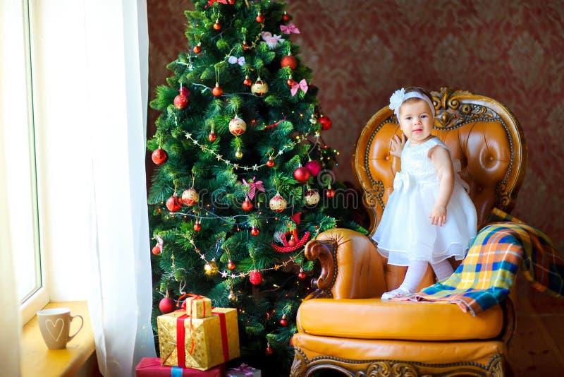 Liten flicka i en härlig klänning nära en festlig julgran royaltyfria bilder