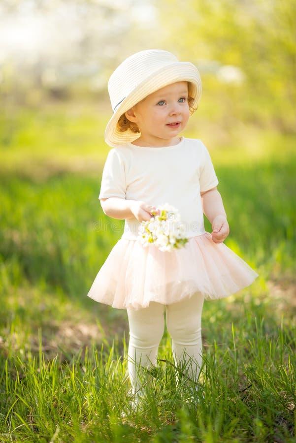 Liten flicka i en hatt och med en blomstra filial som ?r glad, i en blomstra tr?dg?rd eller att parkera Varmt f?r?lskelse-, v?r-  royaltyfri bild