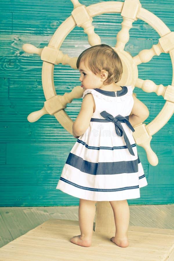Liten flicka i en klänning i sjöman \ 's-stil arkivfoto
