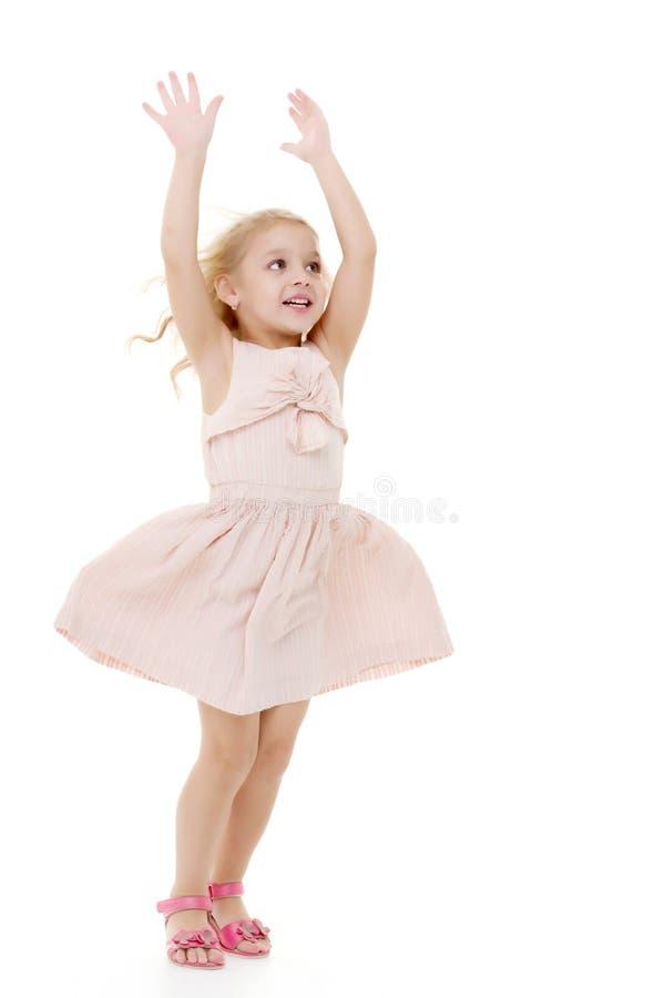 Liten flicka i en klänning som framkallar i vinden royaltyfria bilder