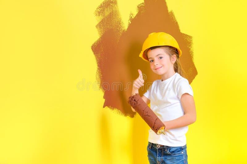 Liten flicka i en konstruktionshjälm med en rulle i händer arkivbilder