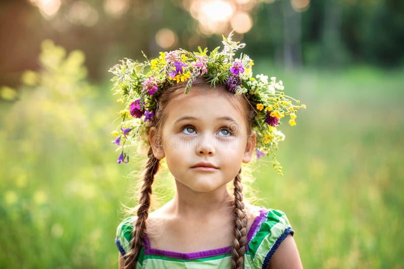 Liten flicka i en krans av lösa blommor i sommar arkivfoto