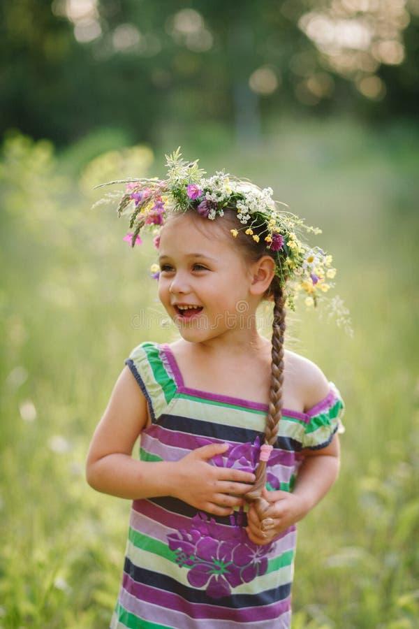 Liten flicka i en krans av lösa blommor i sommar fotografering för bildbyråer