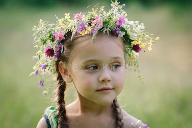 Liten flicka i en krans av lösa blommor i sommar arkivbilder