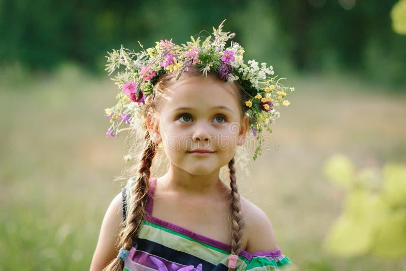 Liten flicka i en krans av lösa blommor i sommar royaltyfria bilder
