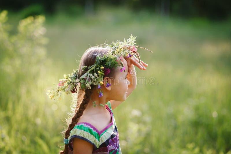 Liten flicka i en krans av lösa blommor i sommar royaltyfri bild
