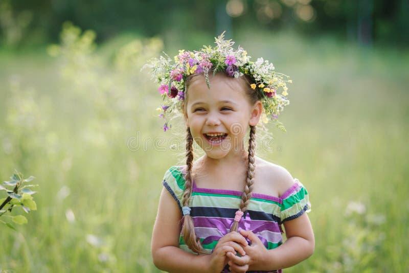 Liten flicka i en krans av lösa blommor i sommar royaltyfri fotografi
