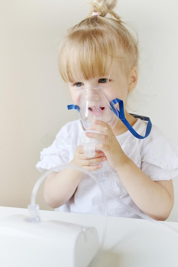 Liten flicka i en maskering för inandningar som gör inandning med den hemmastadda inhalatorn för nebulizer på tabellen royaltyfri fotografi