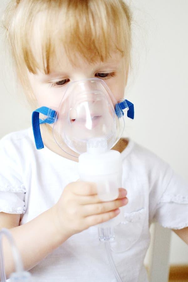 Liten flicka i en maskering för inandningar som gör inandning med den hemmastadda inhalatorn för nebulizer på tabellen arkivfoto