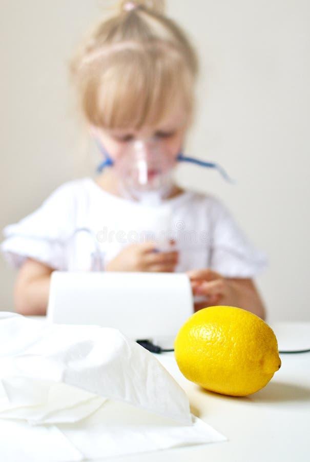 Liten flicka i en maskering för inandningar som gör inandning med den hemmastadda inhalatorn för nebulizer på tabellen fotografering för bildbyråer