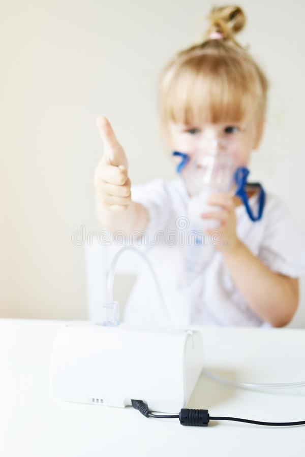 Liten flicka i en maskering för inandningar som gör inandning med den hemmastadda inhalatorn för nebulizer på tabellen arkivbild