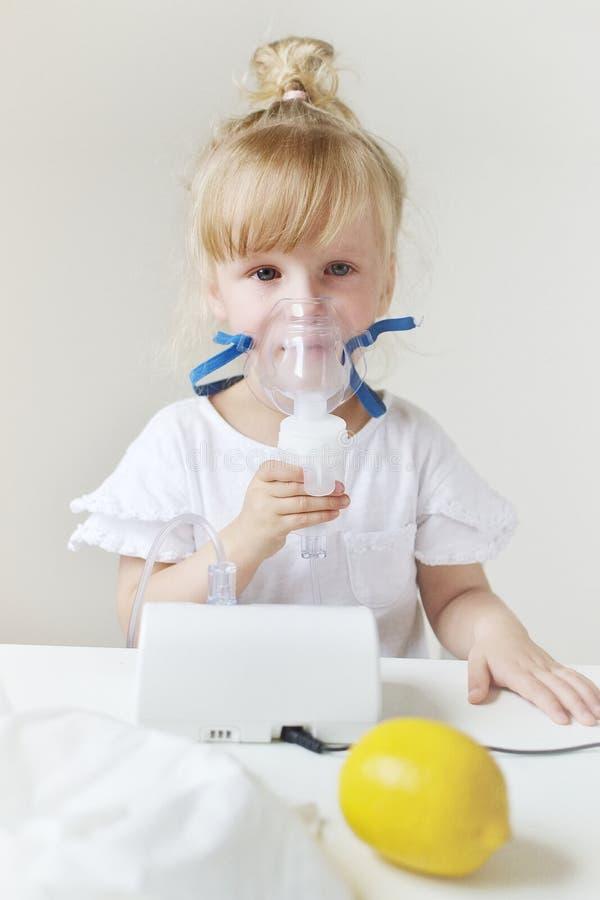 Liten flicka i en maskering för inandningar som gör inandning med den hemmastadda inhalatorn för nebulizer på tabellen royaltyfri foto