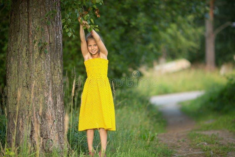 Liten flicka i en parkera nära ett träd Natur royaltyfria bilder
