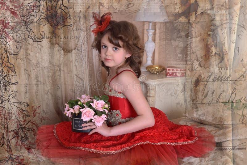 Liten flicka i en röd prinsessaklänning royaltyfria foton